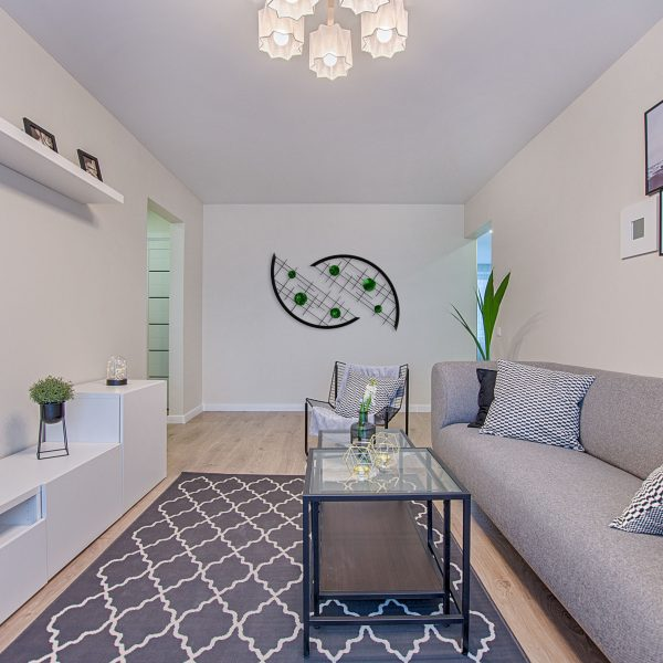 bold green candy and jewel tones accent the black grid arcs in this long narrow modern family room area